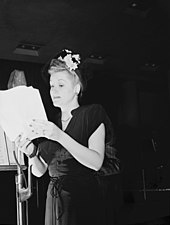 A blonde woman with flowers in her hair, looking at some papers which she is holding in her hands