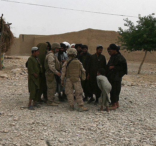 A platoon commander of the 1st Marine Logistics Group, with the battalion interpreter, gather intelligence from local Afghans during a combat logistics patrol to the area, May 9, 2010