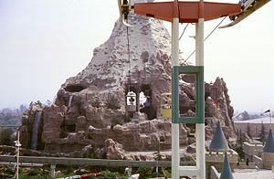 Matterhorn Bobsleds - 1962 from Tomorrowland side. The Matterhorn hid the central Skyway cable pylon. Waterfalls are visible on the left and right sides.