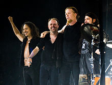 Four men on a stage with their arms behind one another; all are wearing dark clothing
