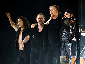 Members of Metallica embracing and smiling onstage