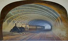 A well-lit railway tunnel recedes into the distance. A train with a steam locomotive and carriages is heading towards the viewer but taking the branch off to the left.