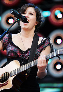 Higgins stands and plays an acoustic guitar with her left hand high on the fret board. She sings into a microphone. Her right arm and bottom of guitar are not in view. Background has large stage lights.