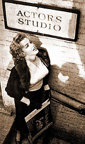 Monroe, who is wearing a skirt, blouse and jacket, standing below a sign for the Actors Studio looking up towards it