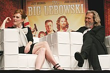 Julianne Moore and Jeff Bridges sitting down, in front of a poster of The Big Lebowski