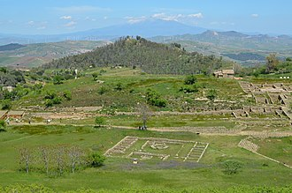 Morgantina - View of Morgantina's Hellenistic agora. An Iron Age settlement was located on the Cittadella hilltop in the background. Mount Etna is seen in the distance.