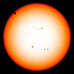 The sun in orange, as seen from the visible spectrum, with Venus in the top left quadrant.