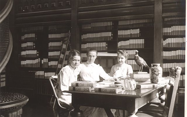 Photograph of three of Nevins Memorial Library's earliest librarians. Seated at the the table in the Reference Room are: Miss Alice Chase, Miss Crosby and Miss Tooday Dorsey.