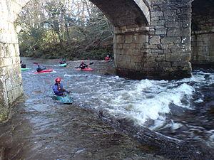 Newbridge, River Dart - Kayakers playing on a wave which forms under Newbridge