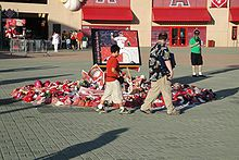 A makeshift memorial outside of a stadium. In the center of the picture are baseball caps, baseballs, and flowers underneath a picture as two people walk by, glancing at the memorial.
