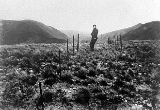 1888 North Canterbury earthquake - This surveyor stands at a fence that crosses the Hope Fault near Glynn Wye Station. The fence, originally straight, has been kinked by the sideways movement of the land.