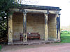 A stone loggia with four columns supporting an entablature, and containing a wooden seat