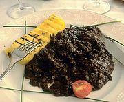 Un piatto di pastissada con una fetta di polenta