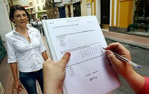 Questionnaire - A researcher asking a woman on the street, while filling a Questionnaire with her answers.