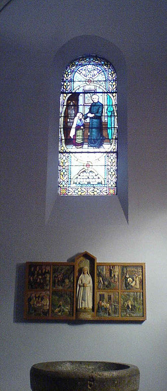 Dominique Peyramale - Stained glass window in the Parish Church in Lourdes depicting an encounter between Peyramale and St. Bernadette. At the bottom of the image is the baptismal font where Bernadette was baptised.The stained glass is by Gabriel Loire.