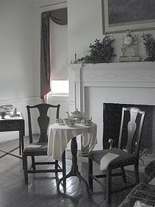 Photograph of a bedroom, showing two chairs and a tea table in front of a fireplace. The room is painted white and the furniture is of a dark wood.
