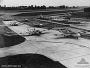 Several jet aircraft parked on the tarmac at an airfield