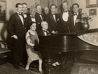 1928 in music - Maurice Ravel at the piano with Éva Gauthier in 1928; George Gershwin listens at right.