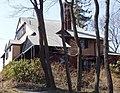 Granda kvant-gabloita domo staras sur monteto malantaŭ kelkaj arboj.