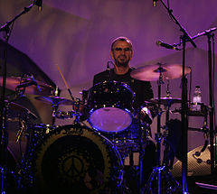 A colour photograph of Ringo Starr playing a dark coloured drum kit on a stage. The background is yellow.
