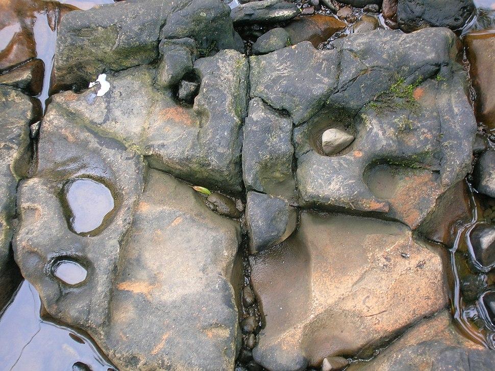 Rock-cut basin and pebbles