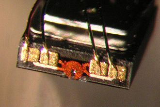 Disk read-and-write head - Microphotograph of a hard disk head. The size of the front face is about 0.3 mm. One functional part of the head is the round, orange structure in the middle - the lithographically defined copper coil of the write transducer. Also note the electric connections by wires bonded to gold-plated pads.