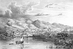 Engraving depicting two small boats sailing into a bay backed by high mountains at the foot of which are the buildings of a town