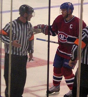 Saku Koivu - Koivu being escorted to the penalty box by two referees during his career with the Montreal Canadiens.