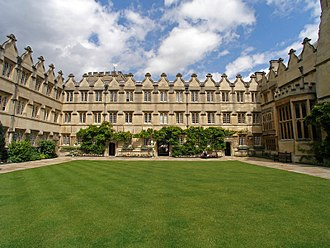 Jesus College, Oxford - A square grass lawn surrounded on three sides by joined buildings; to the left and centre, three storeys with windows positioned to form a regular pattern, topped at roof level above each window by curved gablets; on the right, two bay windows (one large, one medium) project from the wall, with the same design of curved gablets.
