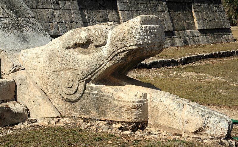 Serpent head at the base of El Castillo.jpg