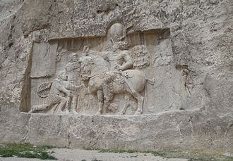 Valerian (emperor) - A bas relief of Emperor Valerian standing at the background and held captive by Shapur I found at Naqsh-e Rustam, Shiraz, Iran. The kneeling man is probably Philip the Arab.