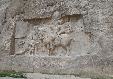 A bas relief of Emperor Valerian standing at the background and held captive by Shapur I found at Naqsh-e Rustam, Shiraz, Iran. The kneeling man is probably Philip the Arab. Shapur victory.JPG