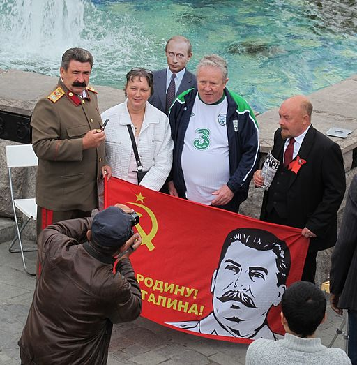 Sosia of stalin and lenin posing with tourists