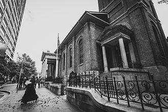 Black and white photo of the rector in black clerical garb striding across the footpath towards Phillip Street