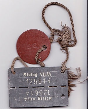 Stalag VII-A - ID tag as worn by POWs. Name and service number are on the brown disc.