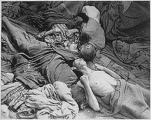 Photo noir et blanc prise dans le camp de Dachau, le 30 avril 1945. D'un fatras de couvertures de différentes nuances de gris, émergent, au centre de la photo, quatre corps décharnés de prisonniers morts de faim. Trois des têtes visibles se rejoignent au centre de la photo.