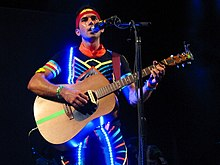 Stevens on-stage wearing a colorful suit and a string of lights while playing guitar and singing into a microphone