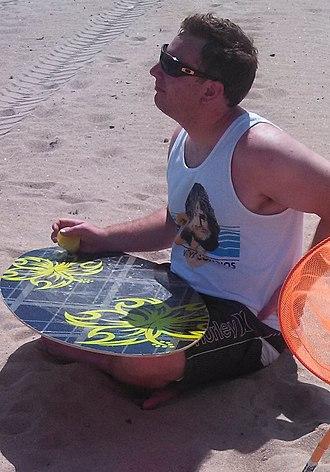 Surfboard wax - Man applies surfboard wax to skimboard at beach.