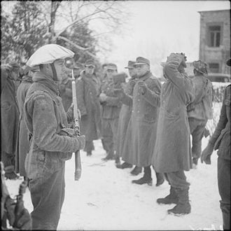 71st Infantry Brigade (United Kingdom) - Men of the 1st Battalion, Ox and Bucks Light Infantry, 53rd (Welsh) Division, guarding German prisoners in the village of Marche in Belgium, 7 January 1945.