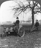 "A black-and-white photo of a man on an (1902 model) ""Ivel"" tractor"