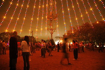 People walking under the Zilker Tree. Christma...