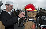 U.S. Navy Electronics Technician 3rd Class Jason Mull, left, instructs the Latvian Youth Guard on how to don firefighting gear June 10, 2013, during a tour aboard the U.S. 6th Fleet command ship USS Mount 130610-N-ZL691-055.jpg