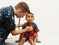 U.S. Navy Hospitalman David Looney listens to an Indonesian child's heart while conducting rounds for a surgery screening at Siloam Hospital June 6, 2012, in Manado, Indonesia, during Pacific Partnership 120606-N-GI544-133.jpg