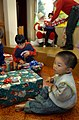 US Navy 021207-N-5961C-004 A young boy from the Elizabeth Saunders Home for orphans opens his Christmas present as Santa and his helper deliver another present to a very happy child in the background.jpg