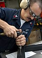 US Navy 040609-N-5313A-002 Aviation Structural Mechanic 1st Class Ronald McCue, from Glen Burnie, Md., drills a hole into a doorframe.jpg