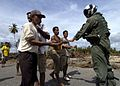 US Navy 050103-N-6020P-145 A U.S. Navy air crewman is greeted by stranded locals as he passes out food.jpg
