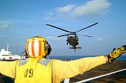 US Navy 050224-N-0357S-103 A Landing Signal Enlisted (LSE) guides a MH-60S Seahawk helicopter, assigned to Helicopter Combat Support Squadron Five (HC-5), for a landing aboard the Military Sealift Command (MSC) hospital ship U.jpg