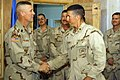 US Navy 051111-N-3750S-007 U.S. Army Command Sgt. Maj. Jeffrey Mellinger, Multi-National Force Iraq, left, recognizes Construction Mechanic 2nd Class Derrick Majchszak's hard work with a hand shake and his command coin.jpg