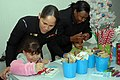 US Navy 061127-N-5459S-019 Personnel Specialist 3rd Class Yahaira Pou helps her niece Alexia design and create a personal Christmas stocking during Operation Christmas at the Army National Guard Armory.jpg