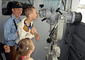 US Navy 070702-N-5621B-007 Boatswain's Mate 3rd Class Christopher Pullon helps a Russian child look through the binoculars during a tour of the Guam-based submarine tender USS Frank Cable (AS-40).jpg
